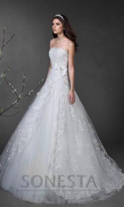 Свадебное платье с лифом прямого кроя и юбкой А-силуэта, покрытой глянцевым кружевом.