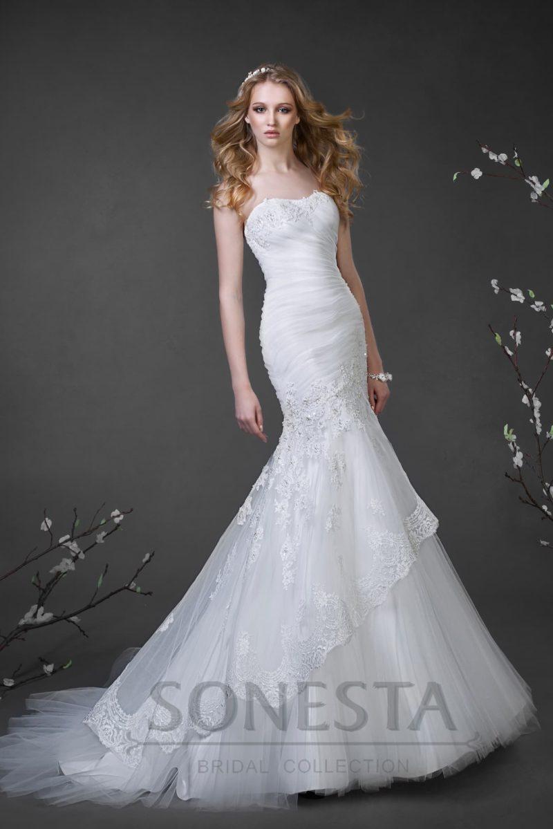 Свадебное платье «рыбка» с крупными драпировками на корсете и юбкой, украшенной кружевом.