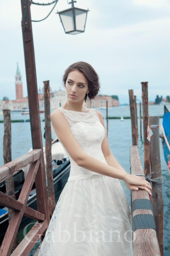 Закрытое свадебное платье с силуэтом «принцесса», декорированное ажурной тканью.
