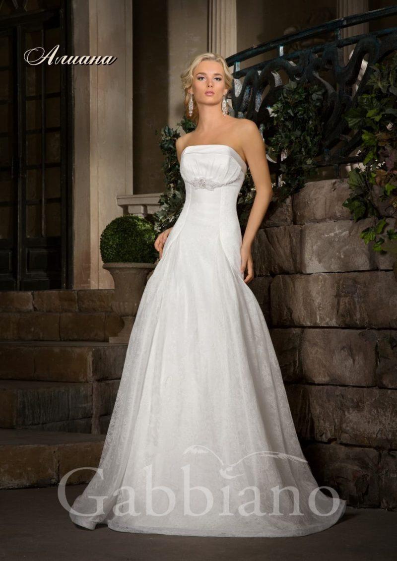 Прямое свадебное платье с открытым декольте, оформленным по краю атласом.