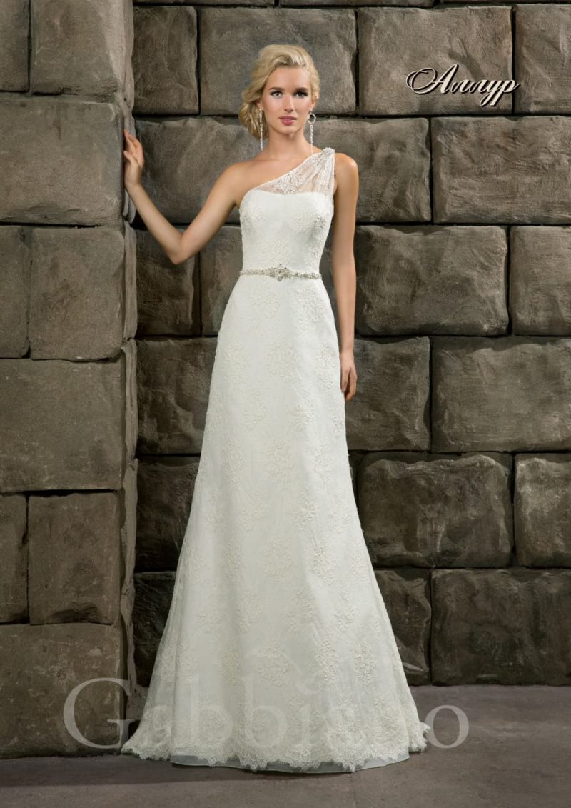 Прямое свадебное платье с узким серебристым поясом на талии и асимметричным верхом.