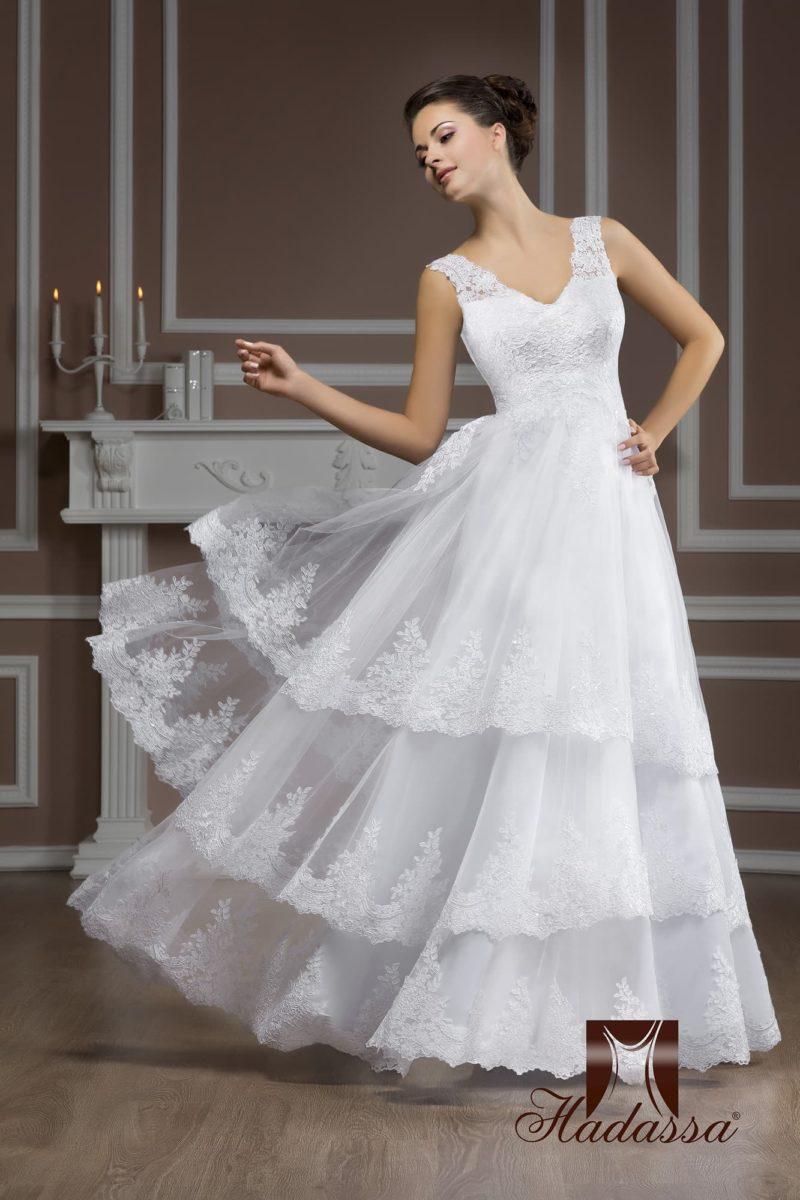 Свадебное платье с V-образным декольте и многоярусной ажурной юбкой А-силуэта.