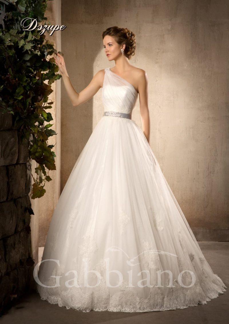 Пышное свадебное платье с асимметричным кроем лифа и кружевной отделкой подола.