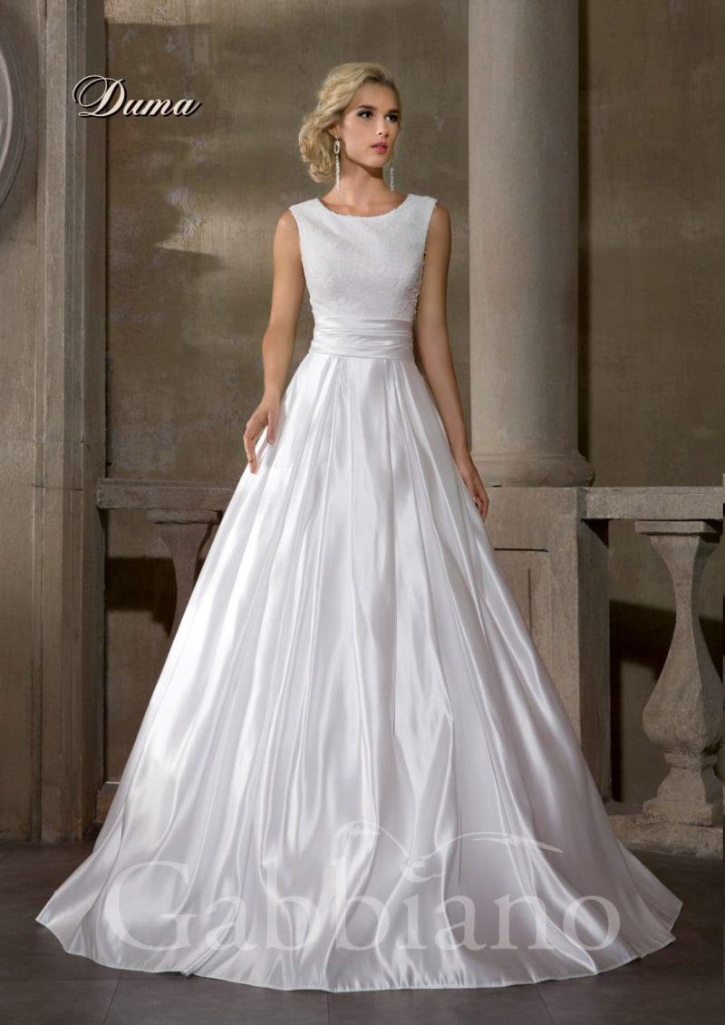 Закрытое свадебное платье с роскошной юбкой А-силуэта, выполненной из атласа.