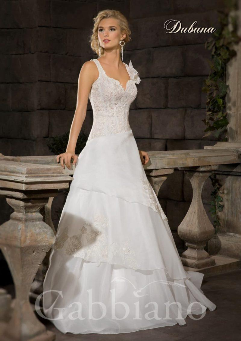 Элегантное свадебное платье с многоуровневой юбкой и открытым корсетом с узкими бретелями.