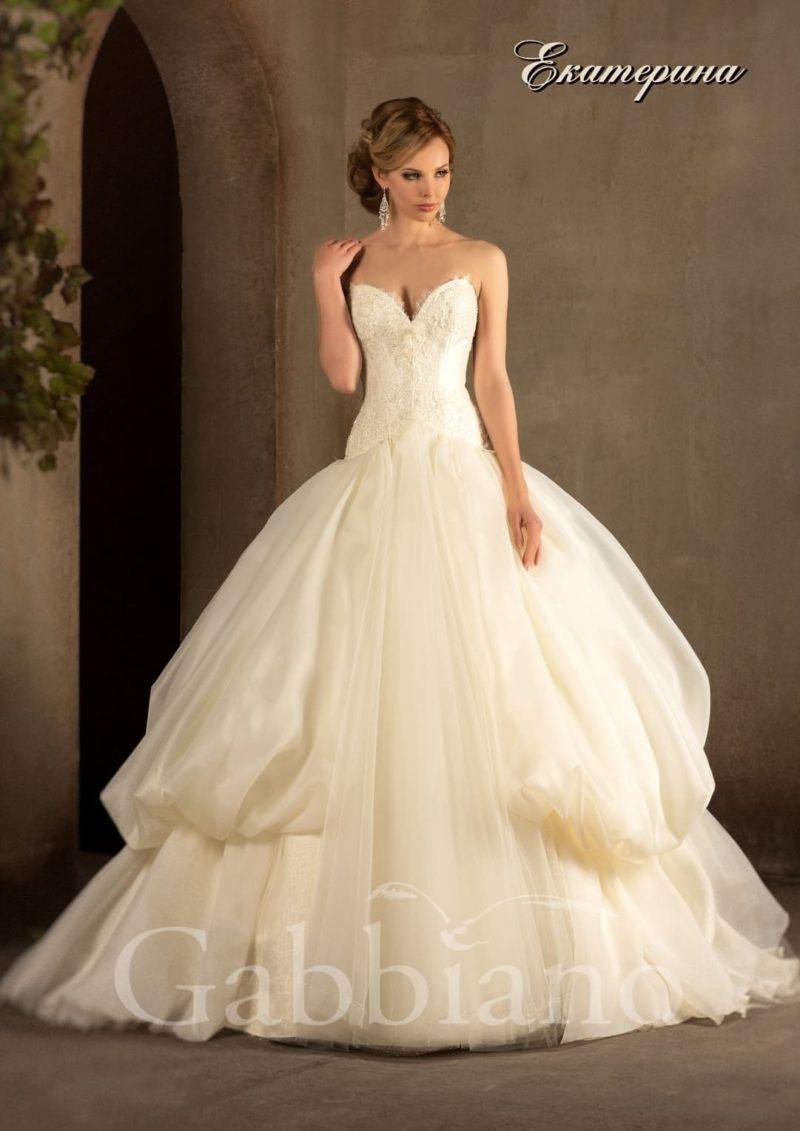 Пышное свадебное платье цвета слоновой кости с заниженной линией талии и открытым лифом.
