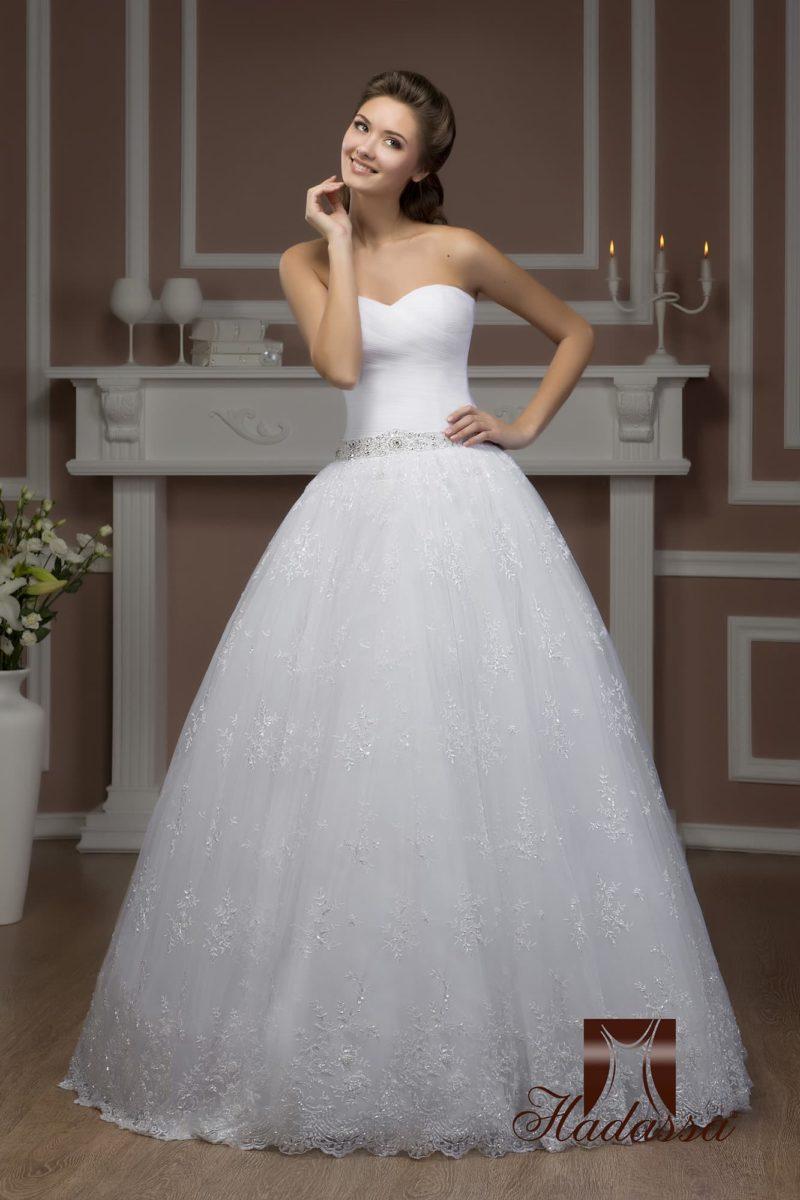 Открытое свадебное платье с роскошной многослойной юбкой пышного силуэта, покрытой кружевом.