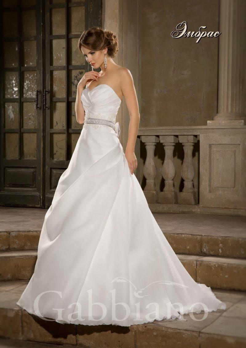 Открытое свадебное платье традиционного силуэта «принцесса» со шлейфом и широким поясом.