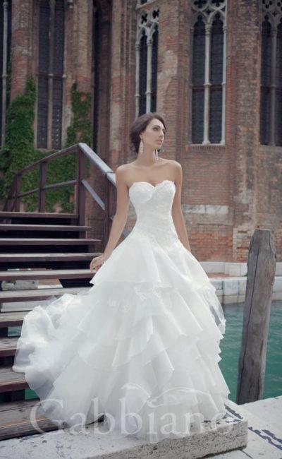 Незабываемо красивое свадебное платье с открытым лифом, юбка которого покрыта оборками.