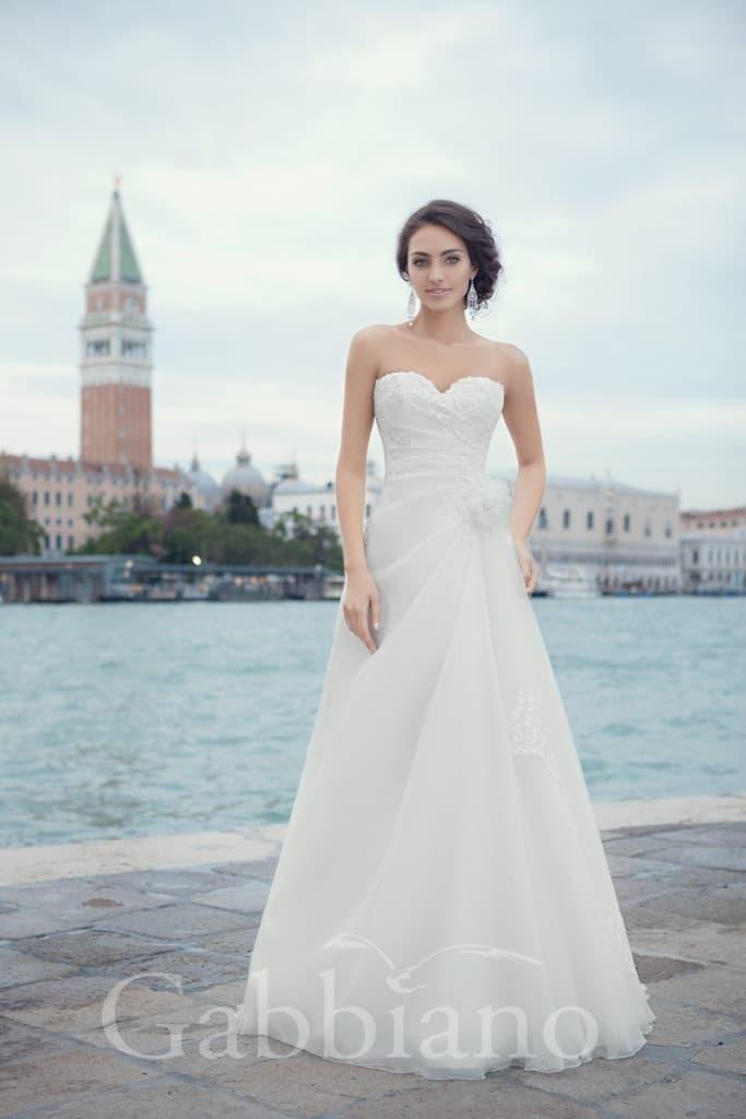Торжественное свадебное платье с силуэтом «принцесса», подчеркнутым волнами ткани шлейфом и открытым лифом.