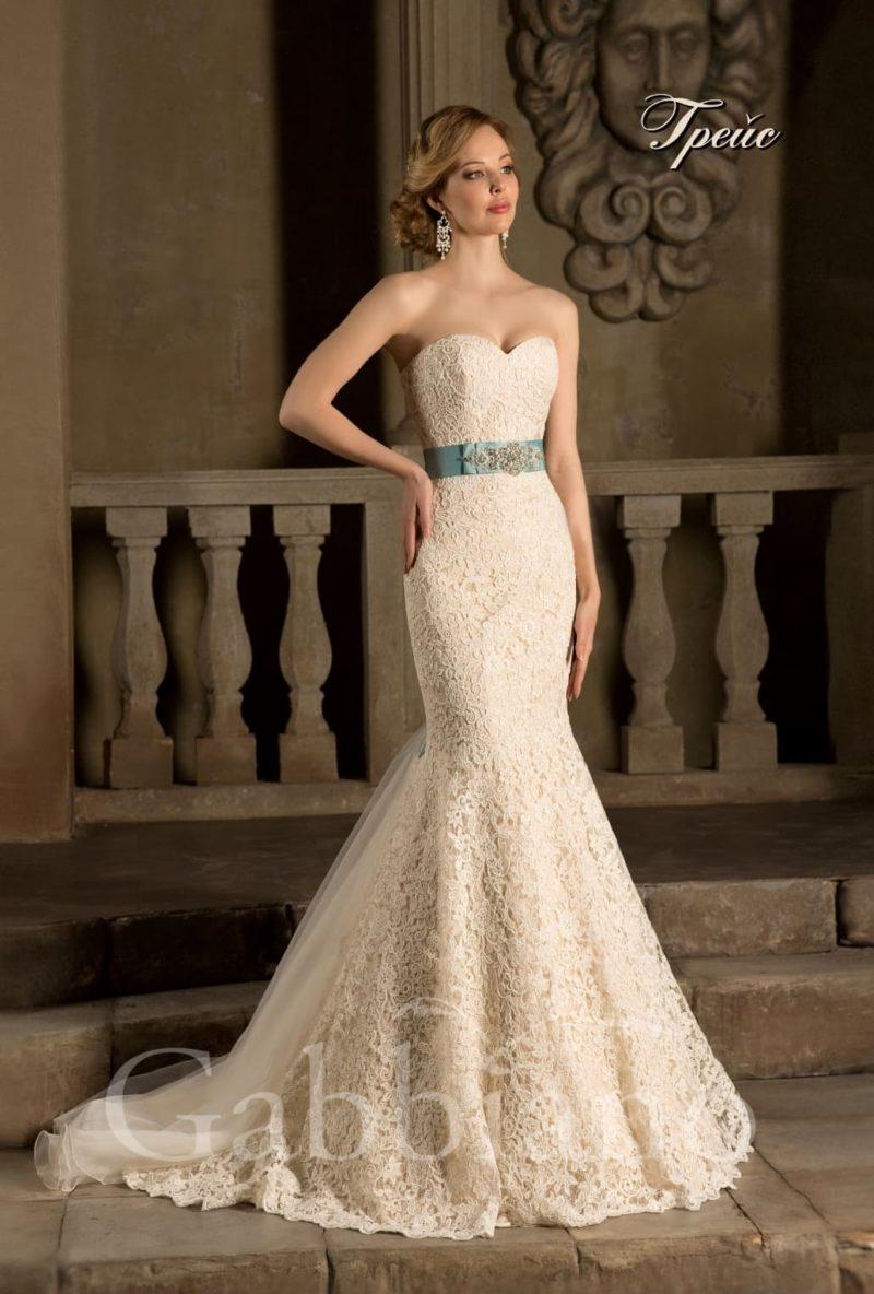 Золотистое свадебное платье силуэта «рыбка» с кружевным декором и бирюзовым поясом.