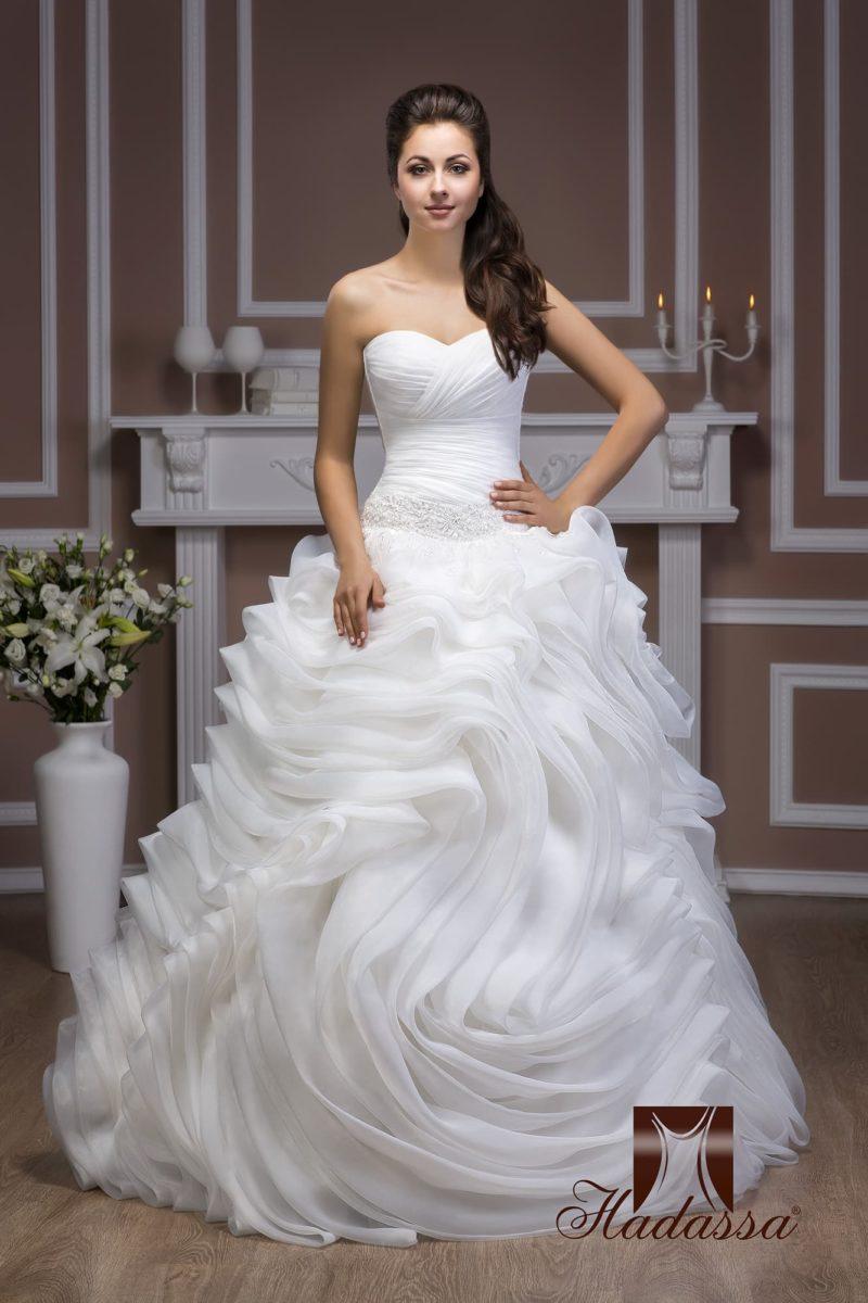 Свадебное платье с романтичным открытым корсетом и роскошной юбкой с множеством оборок.
