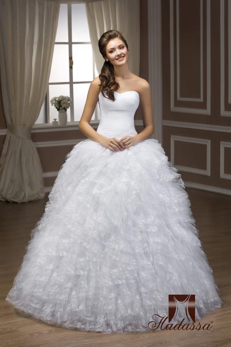 Открытое свадебное платье с лаконичным корсетом и многослойной юбкой с ажурным декором.