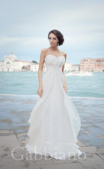 Прямое свадебное платье, декорированное волнами шифоновой ткани от лифа и до подола.