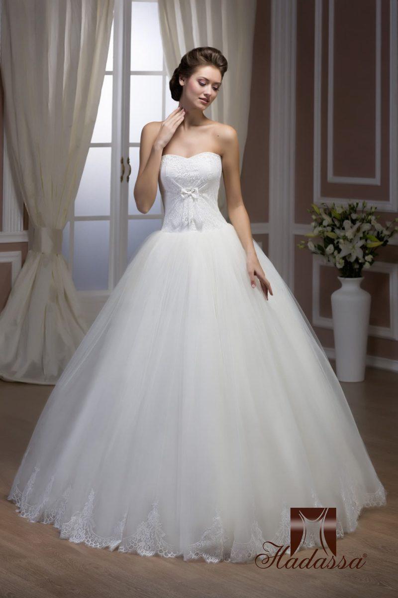 Пышное свадебное платье с бантом на корсете и кружевом по нижнему краю подола.