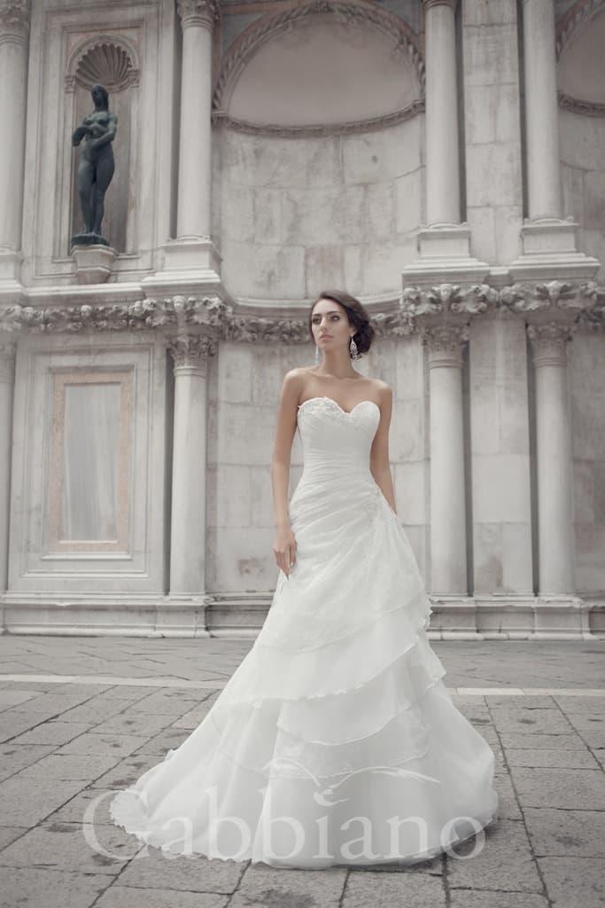 Великолепное свадебное платье с юбкой А-силуэта, покрытой идущими по диагонали волнами ткани.