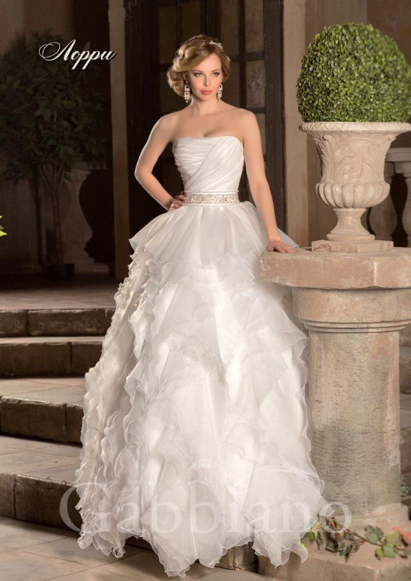 Свадебное платье с объемной юбкой, созданной из пышных оборок, и широким поясом.