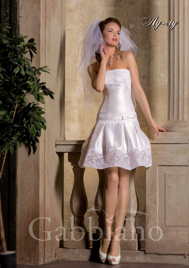Атласное свадебное платье с лифом прямого кроя и необычной пышной юбкой до колена длиной.