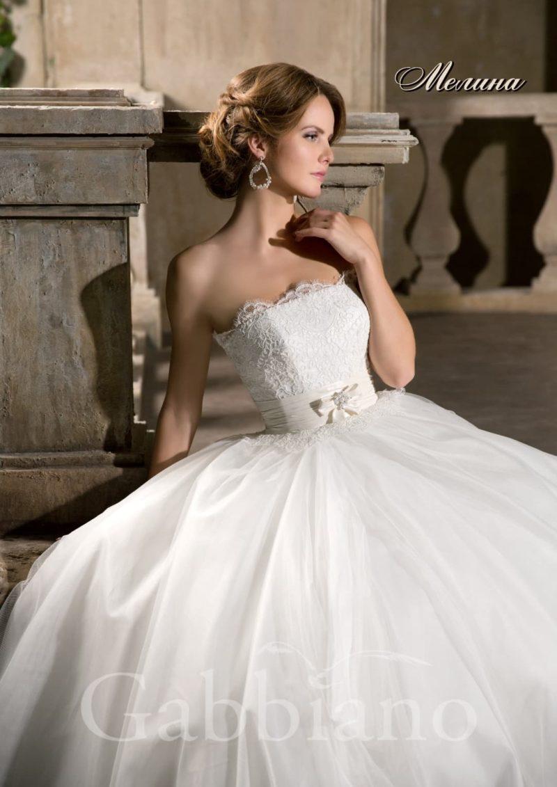 Пышное свадебное платье с открытым лифом прямого кроя, украшенным кружевом.
