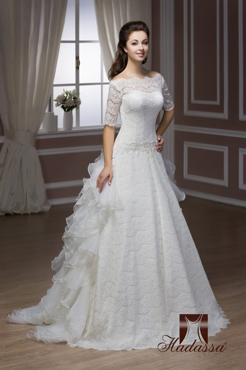 Свадебное платье А-силуэта с фигурным портретным декольте и кокетливым шлейфом из оборок.