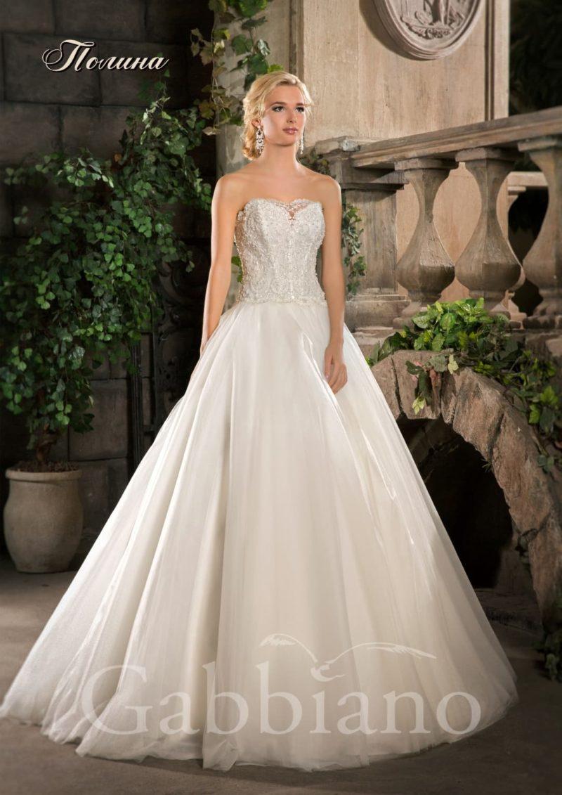 Свадебное платье с пышной юбкой и открытым корсетом, покрытым тонким кружевом.