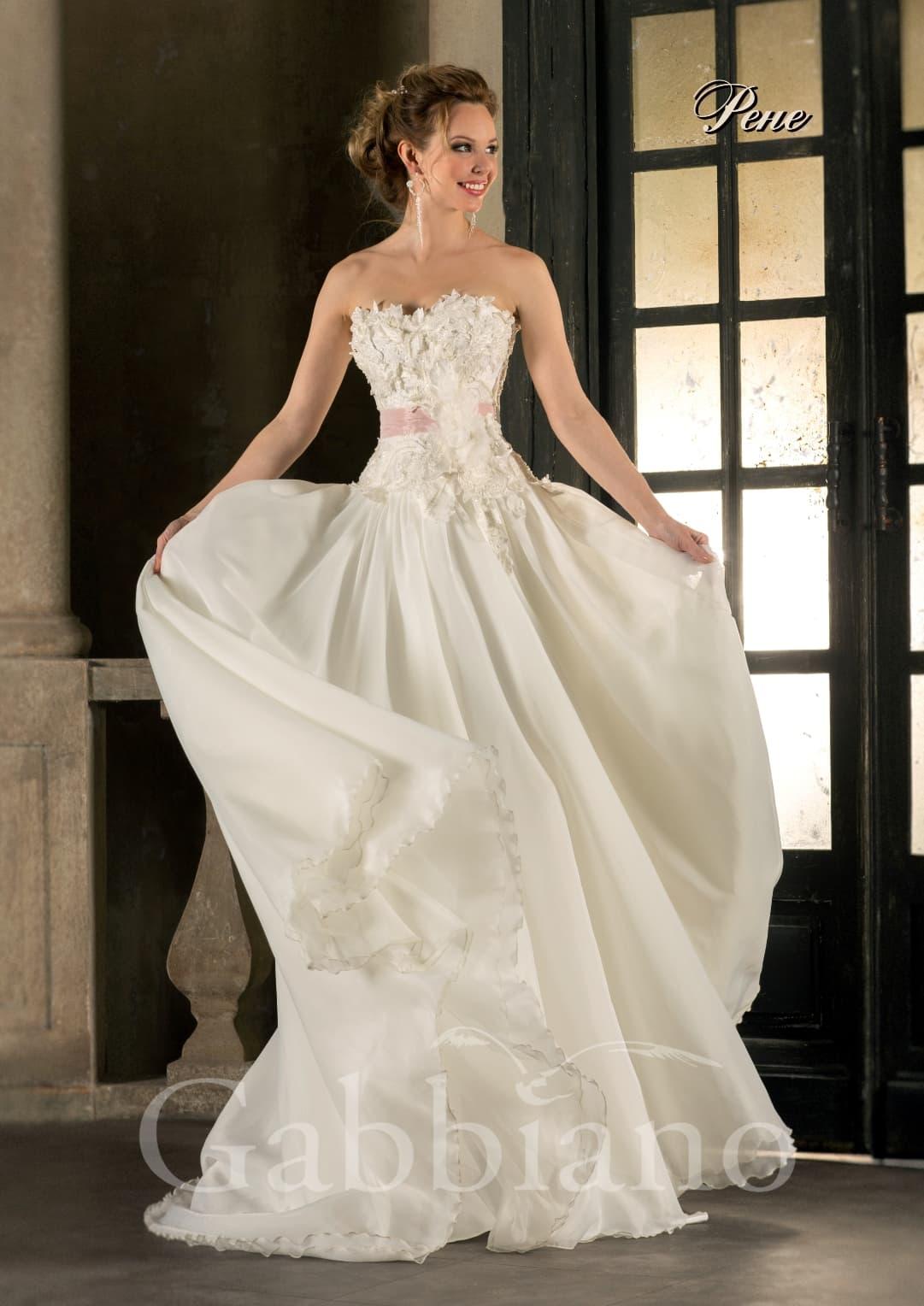 Открытое свадебное платье силуэта «принцесса» с розовым поясом и объемной отделкой лифа.