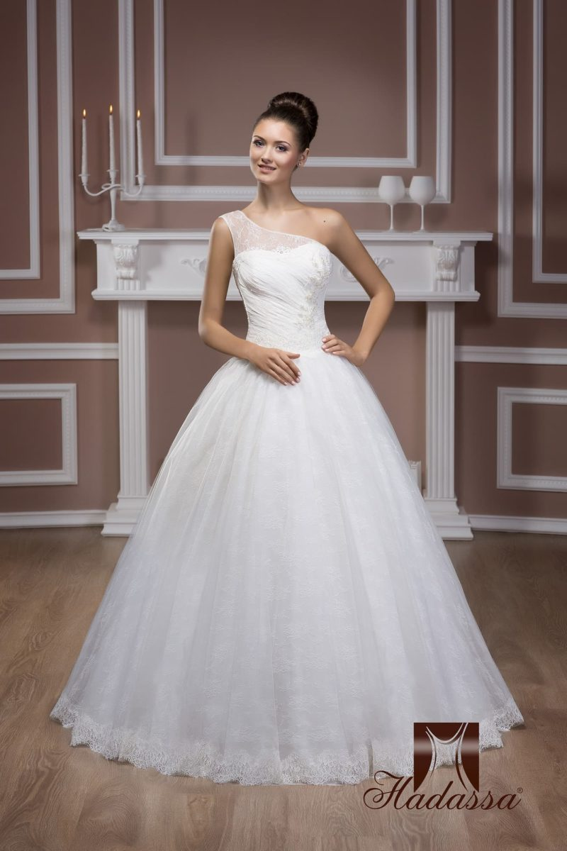 Пышное свадебное платье с кружевным декором подола и асимметричной бретелью.