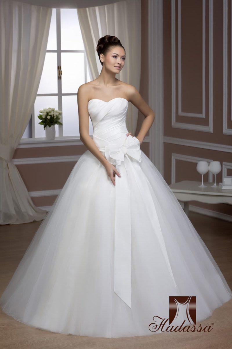 Свадебное платье силуэта «принцесса» с драматичными драпировками и бантом на корсете.