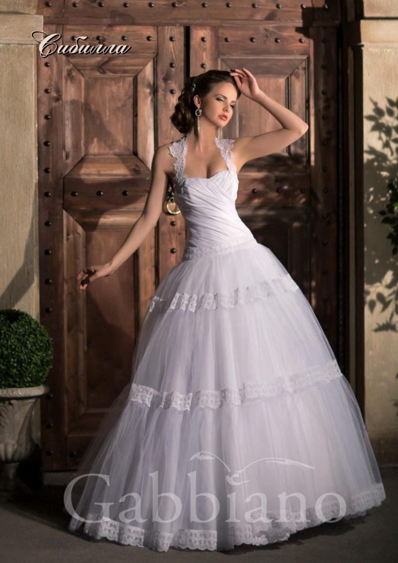 Пышное свадебное платье с горизонтальными полосами кружева по подолу и ажурными бретелями.