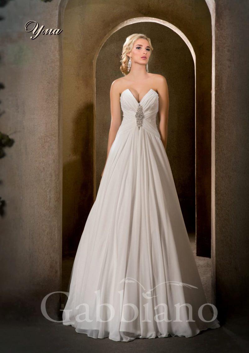 Прямое свадебное платье с драматичным вырезом лифа и декором из драпировок.