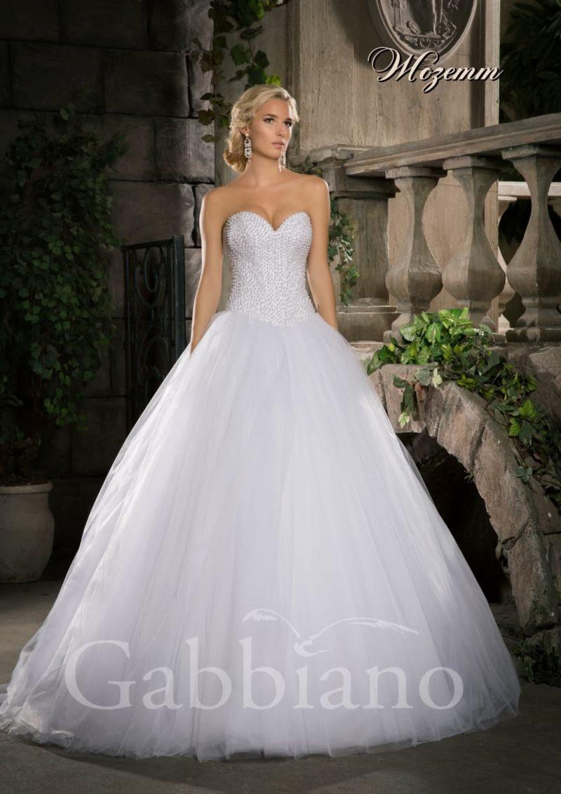 Пышное свадебное платье с открытым корсетом, украшенным бисером по всей длине.