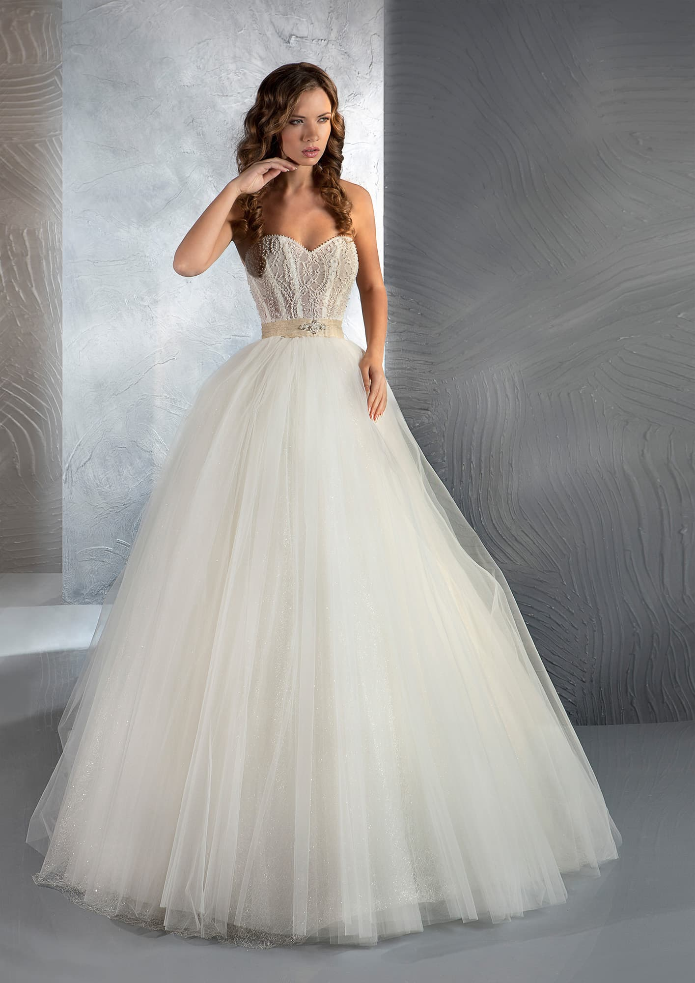 Пышное свадебное платье с открытым корсетом, украшенным вышивкой и атласным поясом.