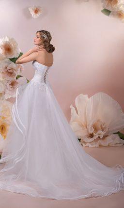 Открытое свадебное платье с глубоким декольте и многоярусной юбкой А-силуэта со шлейфом.