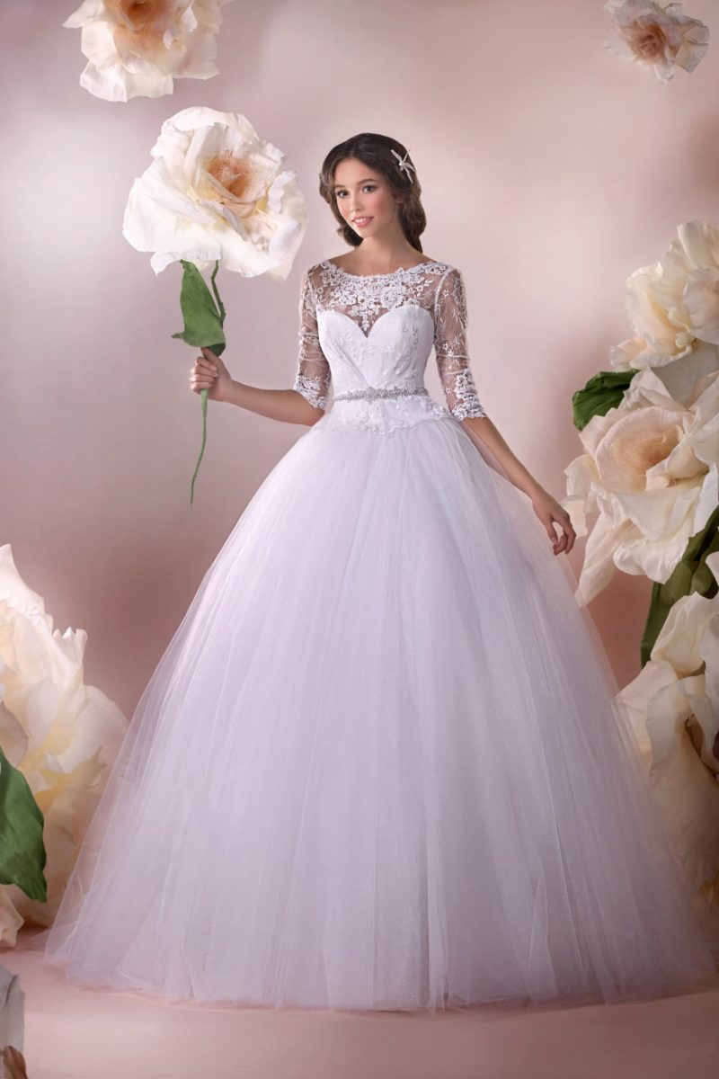 Пышное свадебное платье с ажурным верхом и узким сверкающим поясом на талии.