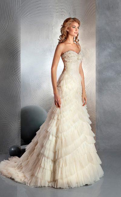 Свадебное платье с открытым лифом и юбкой силуэта «рыбка», покрытой множеством оборок.