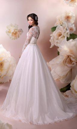 Закрытое свадебное платье с длинными рукавами и шикарной многослойной юбкой со шлейфом.