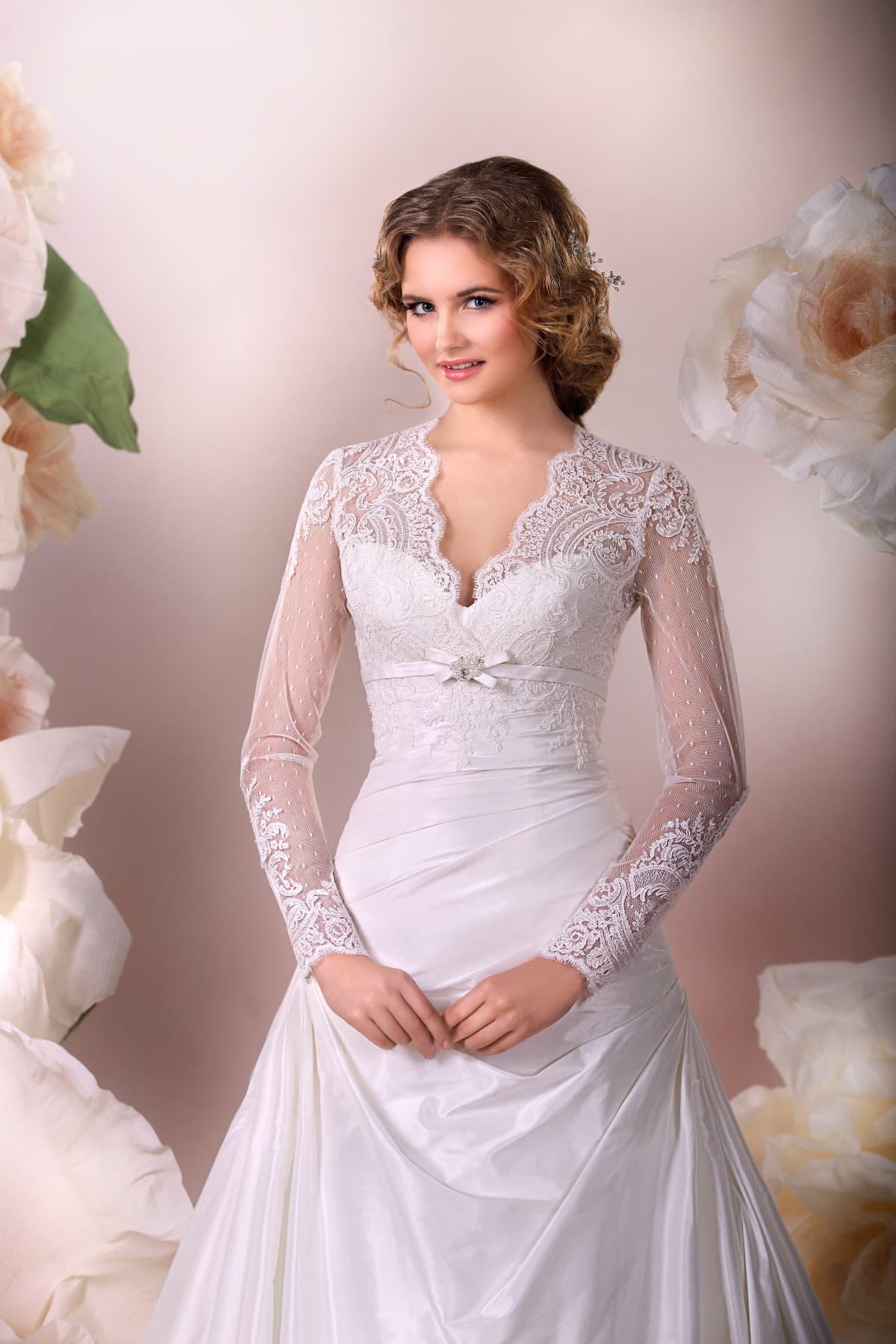 Кружевное свадебное платье с юбкой силуэта «принцесса» и V-образным вырезом лифа.