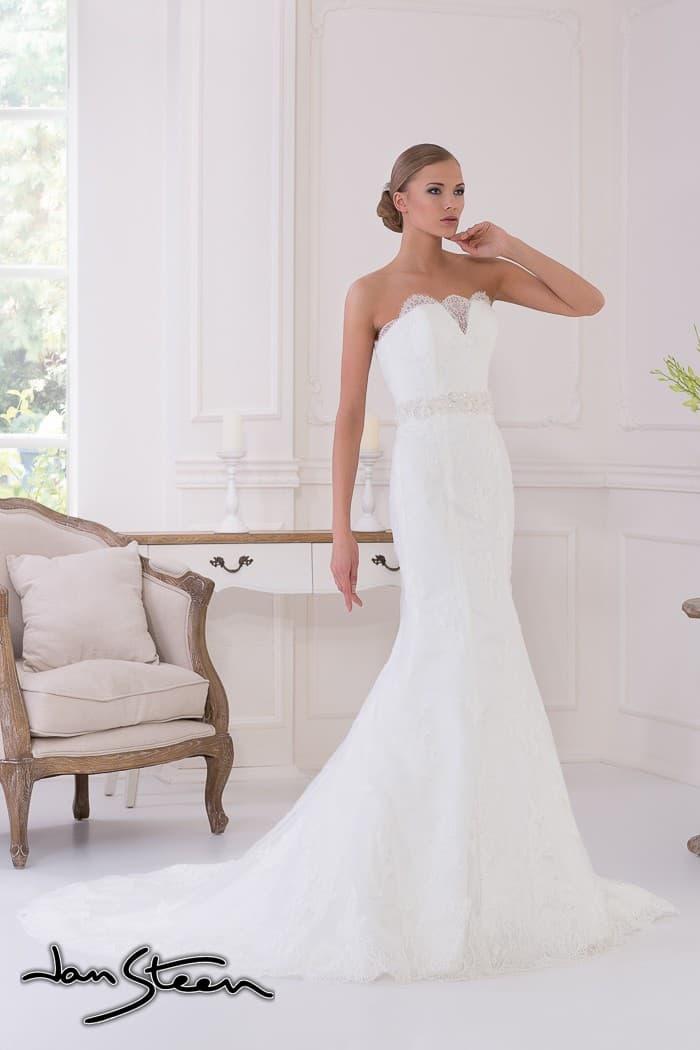 Изысканное кружевное свадебное платье прямого силуэта с длинным шлейфом и открытым лифом.