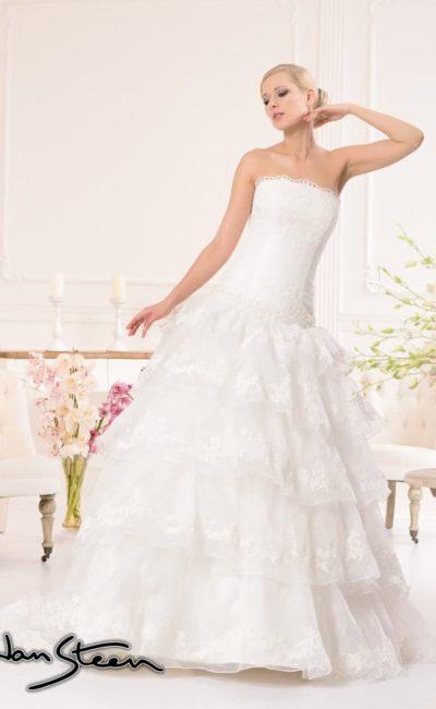 Пышное свадебное платье с заниженной линией талии с многоярусной юбкой из полупрозрачной ткани.