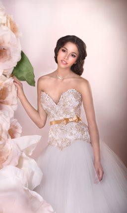 Пышное свадебное платье с открытым корсетом, украшенным золотистой вышивкой.