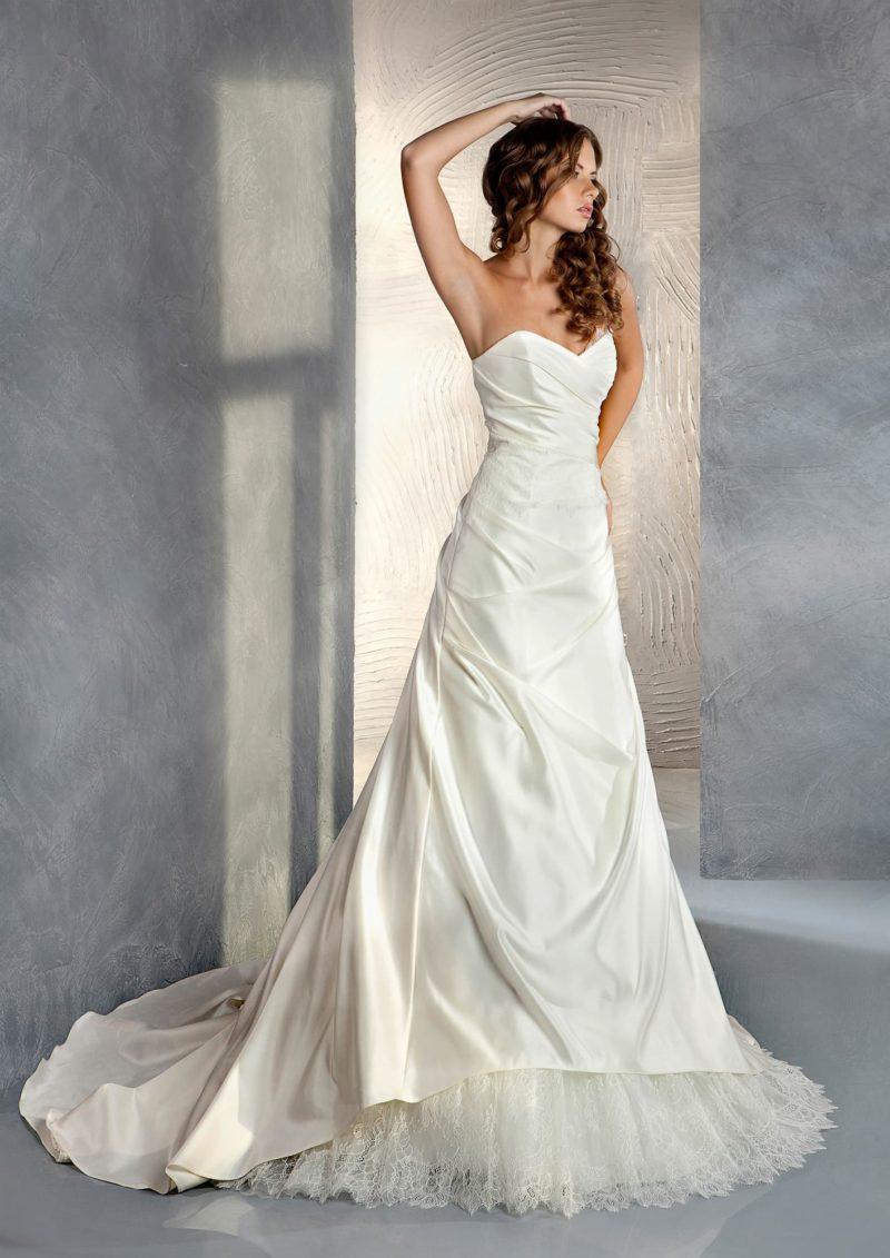 Открытое свадебное платье с длинным шлейфом сзади и декором из роскошных драпировок.