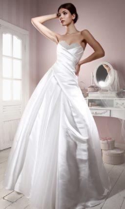 Атласное свадебное платье с пышной юбкой и открытым лифом, украшенным бисерной вышивкой.