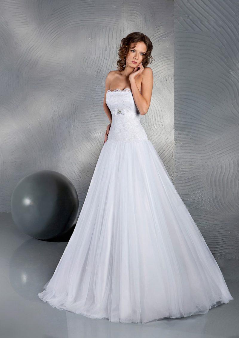 Свадебное платье А-силуэта с открытым лифом прямого кроя, украшенным кружевом.