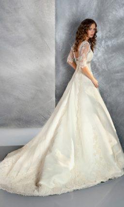 Ажурное свадебное платье силуэта «принцесса» с короткими рукавами и слегка завышенной талией.