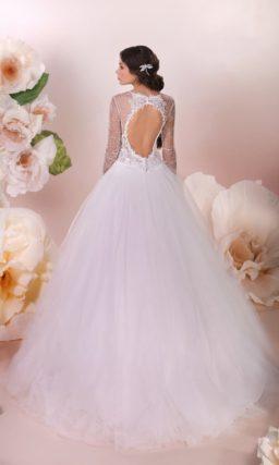 Впечатляющее свадебное платье с пышной юбкой, длинным рукавом и вырезом на спинке.