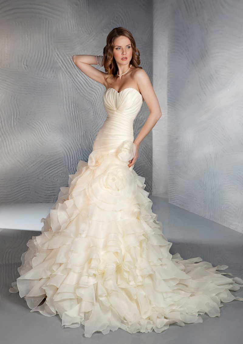 Свадебное платье кремового цвета силуэта «рыбка» с оборками на юбке и шлейфе.