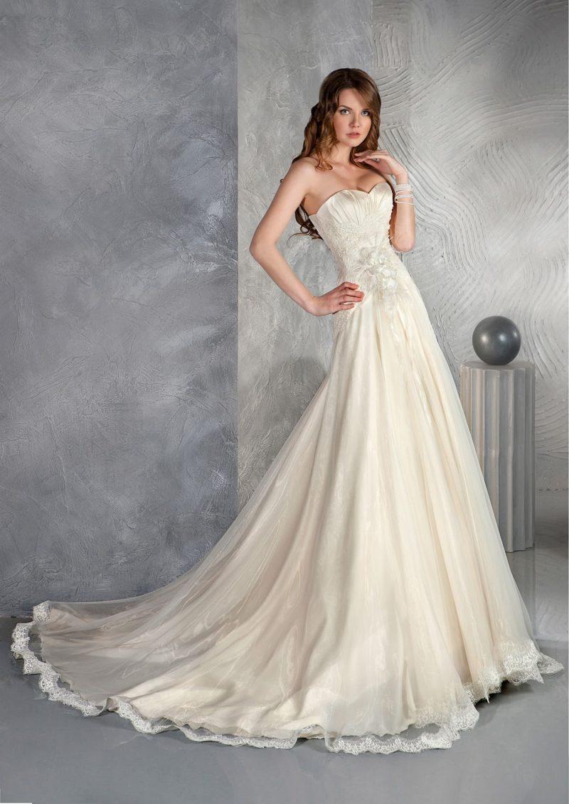 Атласное свадебное платье с лифом в форме сердца и длинным шлейфом юбки А-силуэта.