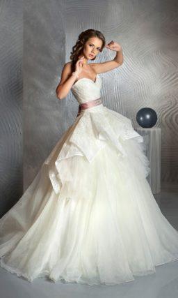 Пышное свадебное платье с цветным поясом и многоярусной юбкой с атласным верхом.