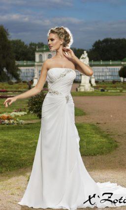 Прямое свадебное платье с драпировками по всей длине и ажурной бретелькой через одно плечо.