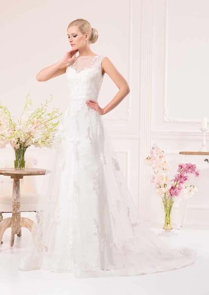 Закрытое свадебное платье А-силуэта с полупрозрачной кружевной верхней юбкой.